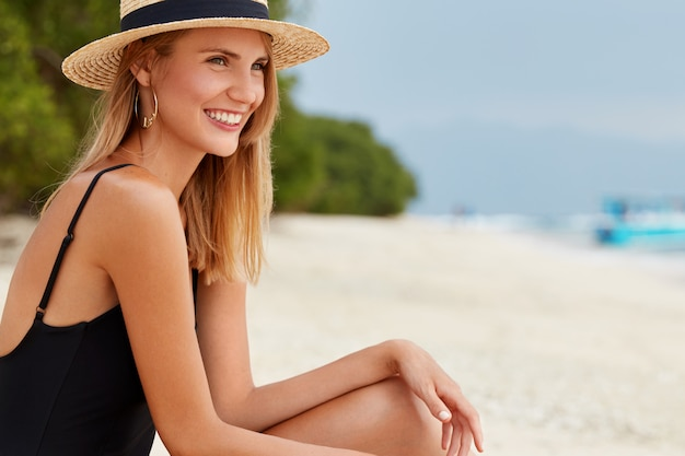 Sideways shot of beautiful delighted woman with tanned healthy skin, wears swim suit and straw hat, spends free time at sandy beach, satisfied to spend summer vacation at resort paradise place