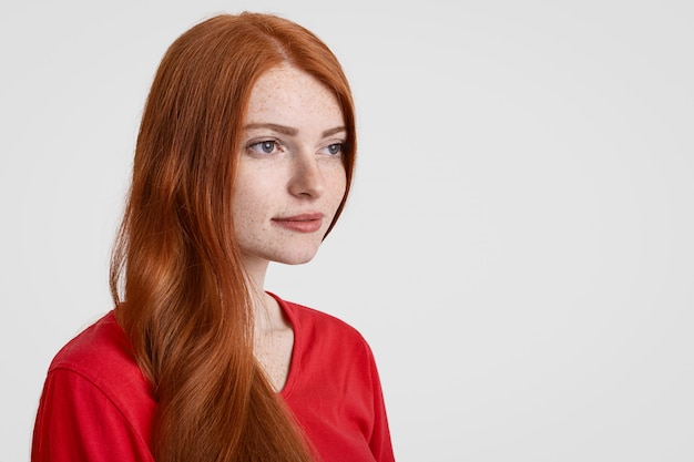 Sideways shot of beautiful red haired freckled woman with long hair