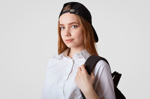 Sideways shot of beautiful schoolgirl wears trendy black cap, white shirt, carries backpack, ready for school and lessons, isolated over white wall school, studying and education concept
