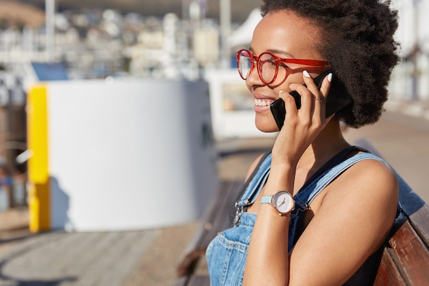 Sideways shot of black ethnic young woman wears spectacles, has telephone conversation, smiles happily, shares impressions about trip with friend, enjoys leisure time, poses over urban setting