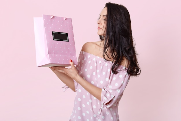 Sideways shot of brunette serious young woman looks at gift bag, wears fashionable summer dress, enjoys recieving present, poses on pink. female makes shoping, stands indoor