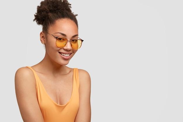 Sideways shot of charming beautiful woman wears trendy shades