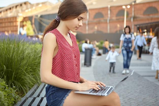 Scatto laterale di affascinante freelance femminile con i capelli raccolti seduto fuori su una panchina con gadget elettronico in grembo, tastiera, connessione 4g per lavoro a distanza, persone che camminano in bakground