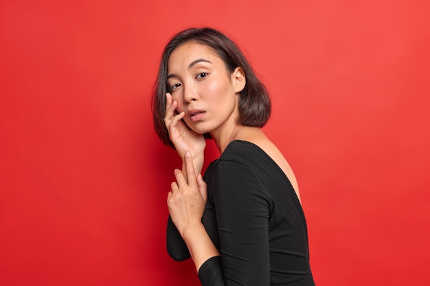 Sideways shot of charming tender young asian woman with bobbed hairstyle keeps hand on face looks seriously at camera wears black dress poses against vivid red wall