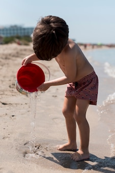 Sideways shot of a child playing with sand bucket