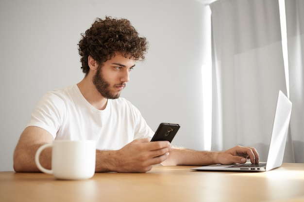 Sideways shot of concentrated attractive young bearded businessman in white t-shirt using laptop and mobile for distant work, having morning coffee, sitting at wooden desk with electronic devices