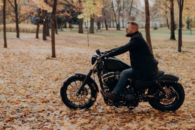 Sideways shot of confident male biker rides motorcycle, has adventure on two wheels in autumn park