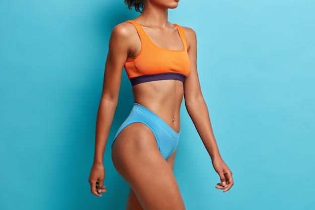 L'inquadratura laterale di una donna dalla pelle scura mostra quanto peso ha perso dopo aver fatto sport ha una figura perfetta indossa modelli di mutandine ritagliate al coperto