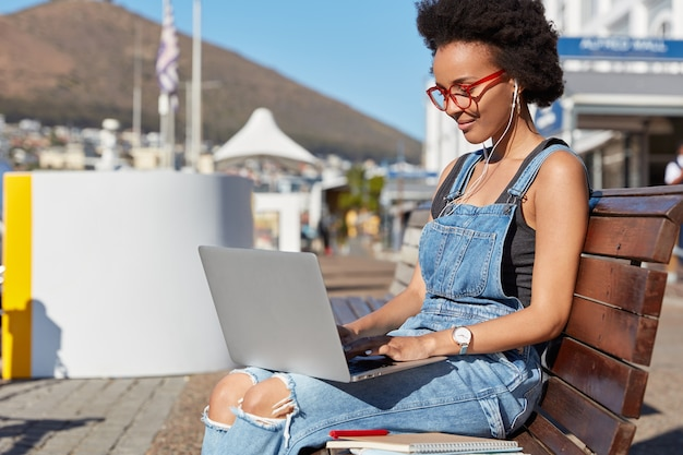 Sideways shot of dark skinned woman with afro haircut, watches video on laptop computer, holds device on knees, sits at bench in fresh air, studies outdoor,