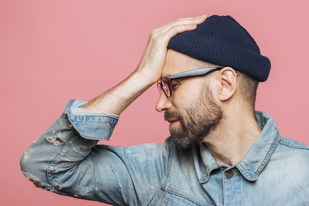 Sideways shot of displeased unhappy man with stubble keeps hand on forehead, closes eyes