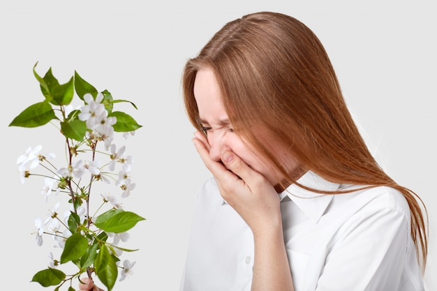 Sideways shot of displeased woman suffers from allergy, stands in front of branch with blossom, sneezes, feels hypersensitivity, dressed in elegant shirt, isolated over white wall sickness