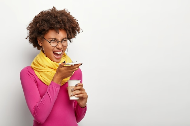 Sideways shot of emotional dark skinned woman with curly hairdo, uses voice recognition app on modern cell phone, holds takeout coffee, wears spectacles, rosy turtleneck, poses over white wall