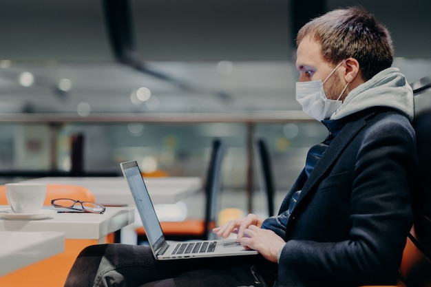 Sideways shot of freelancer keyboards on laptop computer, works on distance, wears protective medical mask during quarantine because of virus outbreak, poses in coffee shop, warns contagious disease