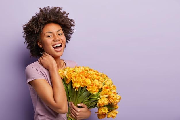 Inquadratura laterale di una donna felice dalla pelle scura che ride di gioia, tocca il collo, tiene i tulipani gialli, indossa una maglietta viola, compiaciuta di ricevere fiori e complimenti, posa sul muro viola, spazio libero