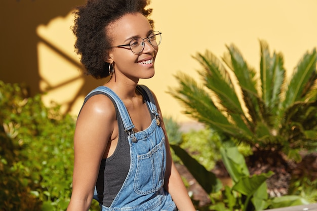 Sideways shot of glad jubilant teenage girl has afro hairstyle, wears round spectacles, jean overalls, poses outdoor over tropical view, yellow wall, free space for your advertising content.