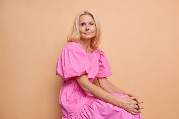 Sideways shot of good looking blonde middle aged woman with natural beauty wears fashionable pink dress