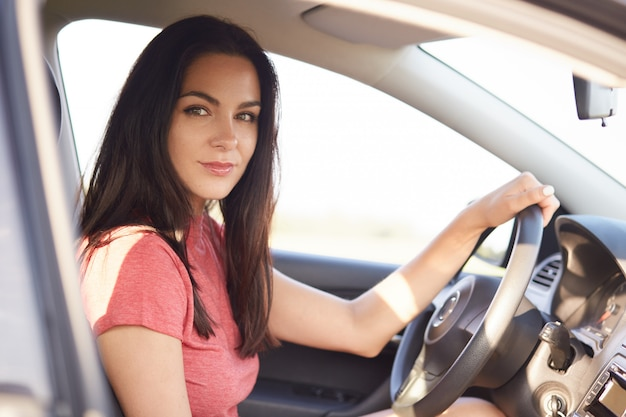 Sideways shot of good looking serious brunette girl drives car professionaly