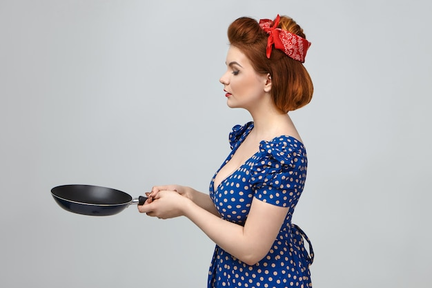 Colpo laterale della splendida giovane casalinga europea che indossa abiti vintage e acconciatura retrò che cucina in cucina, tenendo la padella con entrambe le mani davanti a lei come se stesse per lanciare frittelle