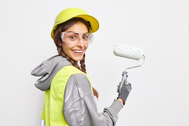 Sideways shot of happy female construction worker smiles gladfully being busy painting