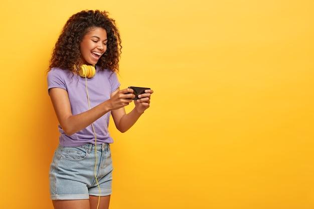 Colpo laterale di una donna felice con i capelli ricci, tiene il cellulare, guarda film divertenti online, ha un sorriso positivo sul viso