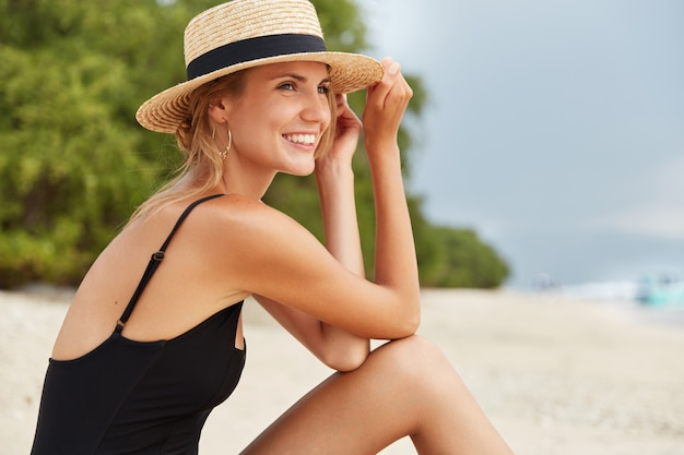 Sideways shot of happy lovely young female tourist wears black swimwear and summer hat, sunbathes on beach, admires wonderful ocean view, has positive expression. people and recreation concept
