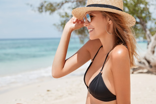 Sideways shot of happy relaxed female tourist wears straw hat, black bathing suit and sunglasses, looks into distance and admires wonderful view breathe ocean breeze, spends vacation on tropical beach