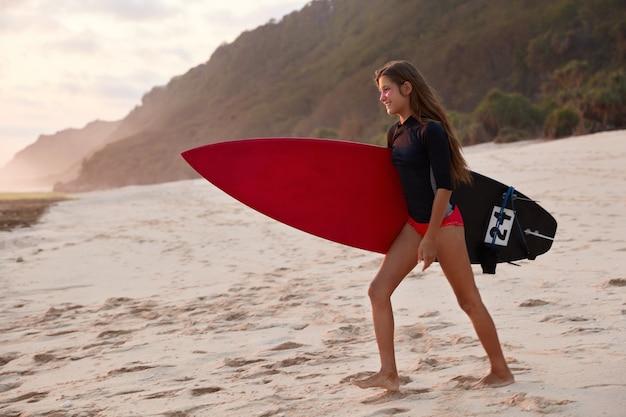 Colpo laterale di donna felice in muta, trasporta la tavola da surf, cammina sulla sabbia