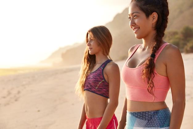 Снимок сбоку привлекательных женщин смешанной расы в повседневном топе со спортивными телами