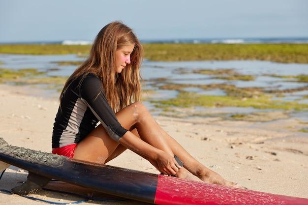 魅力的なスリムな若い女性サーファーの横向きのショットは、岩の多い海岸線に衝突するのを防ぐことができる脚に鎖を固定します