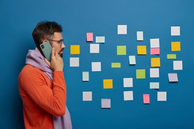 Бородатый парень сбоку разговаривает по телефону, использует современный мобильный телефон, носит очки, стильный костюм, позирует на фоне синей стены.