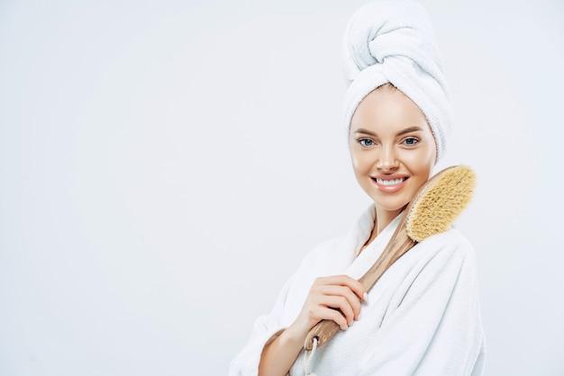 Снимок сбоку красивой молодой европейской женщины с очаровательной улыбкой, позирующей с предметом для ванны, массажирующей тело кисточкой, позирующей на белой стене, пустое место для вашего рекламного контента