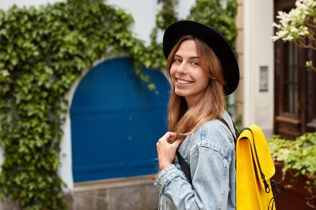 Жизнерадостная милая женщина в модной шляпе и джинсовой куртке, сбоку, идет по старой улице с зеленой растительностью.