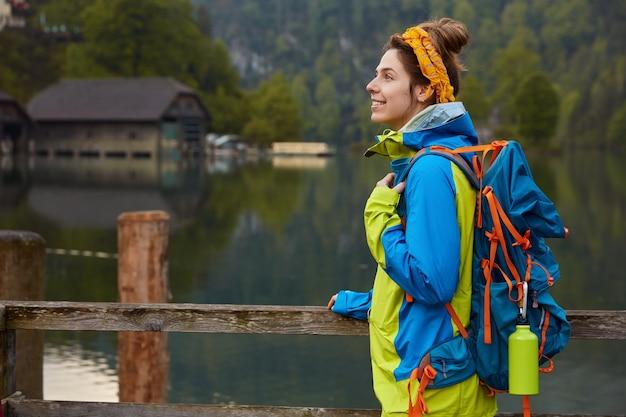 Боковой снимок веселой женщины-путешественницы стоит на деревянном мосту у реки или озера с домиком вдалеке, дышит свежим воздухом, наслаждается природой