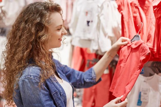 Боковой снимок кудрявой молодой мамы выбирает футболку для своей маленькой дочери, которая в хорошем настроении любит ходить по магазинам