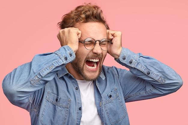 Снимок сбоку: отчаянный стрессовый парень держит кулаки в висках, сердито кричит, недовольно хмурится, выражает негативные чувства