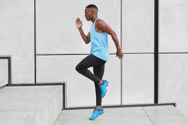 단호한 아프리카 계 미국인 스포츠맨의 옆쪽 샷은 계단을 오르고, 호흡 부족을 극복하기위한 목표를 가지고 있으며, 조끼와 운동화를 착용하고, 흰 벽 위에 포즈를 취합니다. 선수 스포티 한 젊은 남자 단계에서 점프