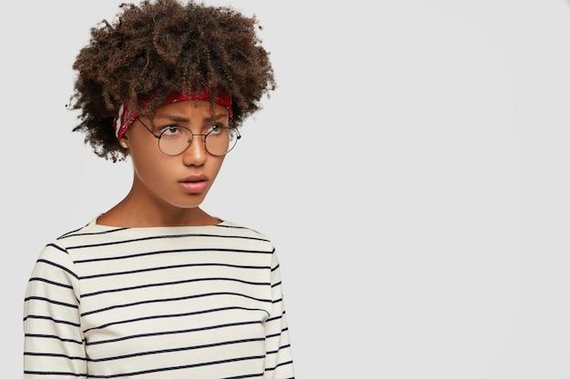 Снимок сбоку: недовольство темнокожей женщины серьезно смотрит вдаль
