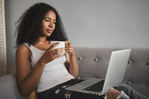 ファッショナブルで魅力的な若い暗い肌の女性の横向きのショットは、破れたジーンズを着て、ソファでリラックスし、ポータブルコンピューターを膝の上に置き、コーヒーを飲み、お気に入りのテレビシリーズをオンラインで見ています。