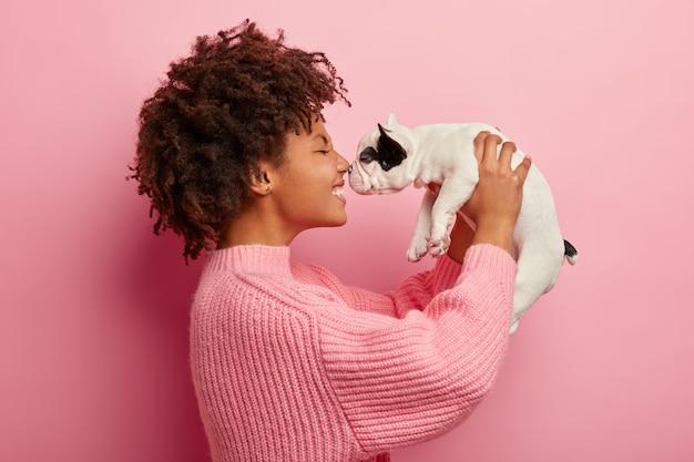 기쁜 아프리카 미국 개 안주인의 옆쪽 샷이 작은 귀여운 강아지와 함께 코를 만집니다.