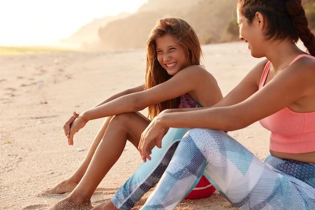 Боковой снимок довольной девушки и ее матери позируют на теплом песке, сидя на фоне утеса