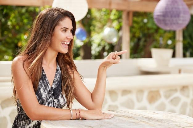 Снимок сбоку симпатичной веселой молодой женщины, которая веселится в спокойном кафе, показывает указательным пальцем вдаль, что-то показывает, у нее счастливый взгляд, летние каникулы в жаркой курортной стране