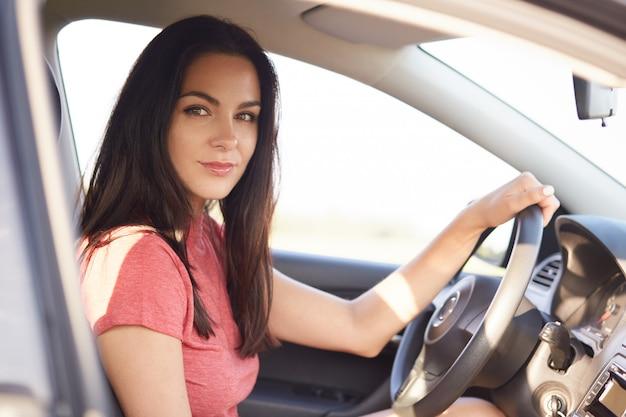 格好良い深刻なブルネットの少女の横向きのショットは、プロの車を運転します