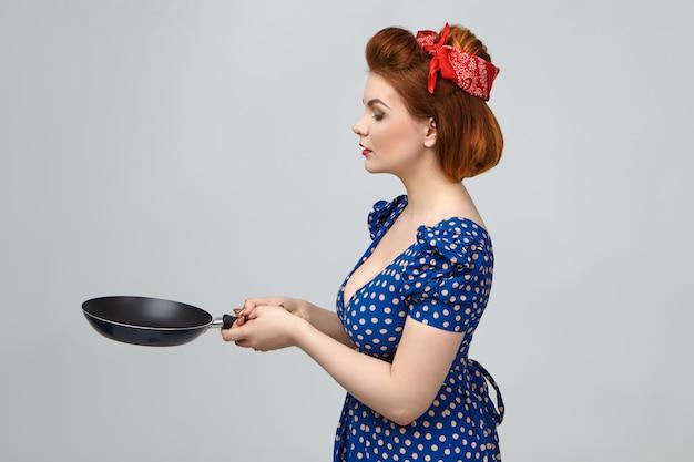 キッチンでヴィンテージのドレスとレトロな髪型の料理を身に着けているゴージャスな若いヨーロッパの主婦の横向きのショット、パンケーキを投げるつもりであるかのように彼女の前でフライパンを持っています