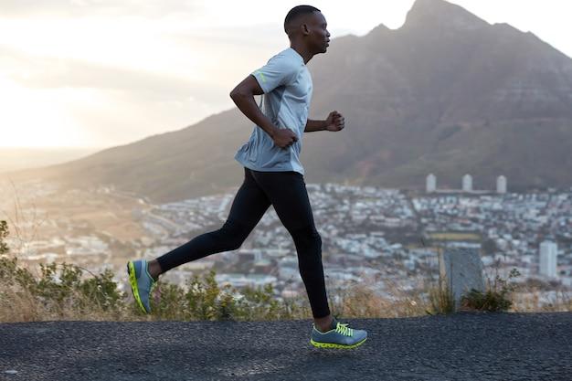 ハンサムなアクティブな男性の横向きのショットは、山の美しい風景に向かって走り、動きのある写真を撮り、トレーニングを楽しんで、非常に速くてエネルギッシュで、スポーツ服を着ています。外のアスリート黒人男性