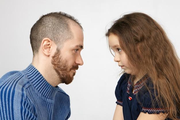 Боковой снимок красивого молодого человека с щетиной, позирующего у белой стены со своей маленькой дочерью, смотрящих друг на друга и спорящих