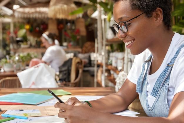 幸せな黒人の金融業者の横向きのショットは、カフェテリアで紙の仕事をします