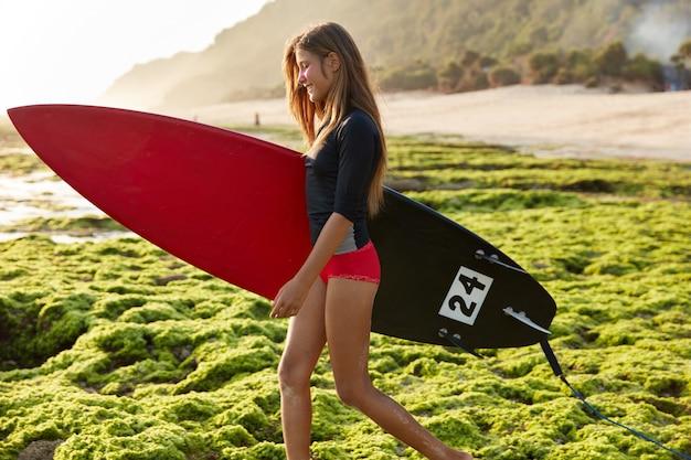 녹색 식물로 덮인 해안선을 가로 질러 걷는 동안 행복한 유럽 소녀의 옆쪽 샷이 긍정적으로 미소 짓습니다.