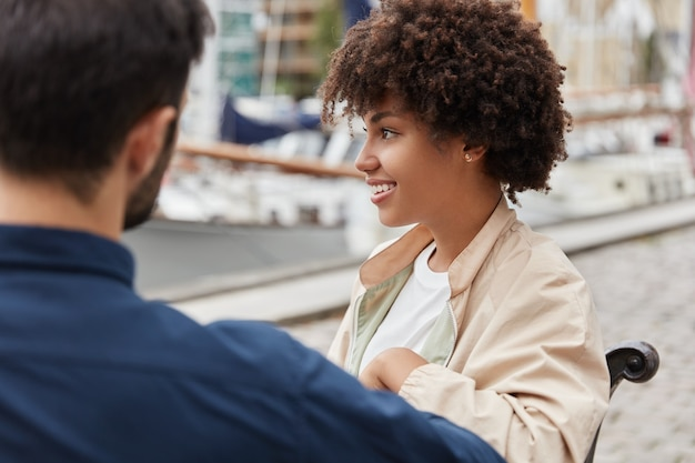 행복한 여자 친구와 남자 친구의 옆쪽 샷은 함께 시간을 보내고 항구 근처에 앉아 인생 목표에 대해 이야기합니다.
