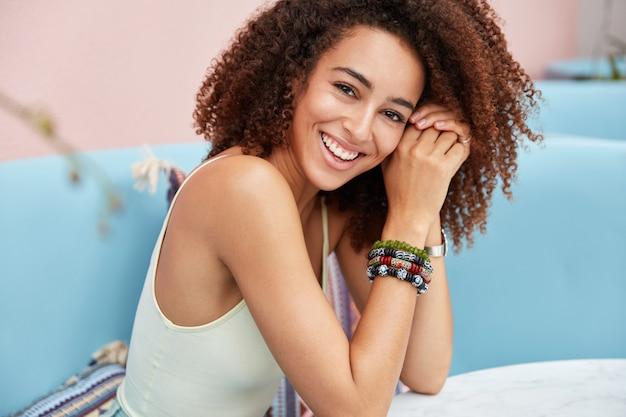 Снимок сбоку довольной смуглой молодой девушки с вьющимися волосами, широкой улыбкой, одетой в повседневную одежду.