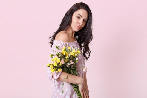 健康的な肌を持つ深刻な暗い髪の女性の横向きのショットは、ファッショナブルなドレスを着た花束を保持し、パステルピンクでポーズします。春が来る。国際婦人デー